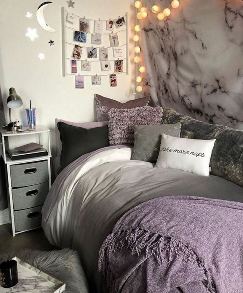 Girls room decor with white gray mattress, purple blanket combined with colorful pillows, decorative fabric walls and round string lamps on the wall