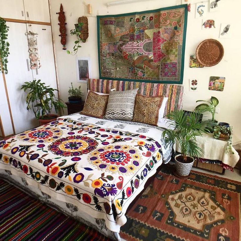 Interesting boho bedroom style with colorful floral motifs on white blankets, patterned pillows, classic wall art fabric tan green plants to complement the decoration