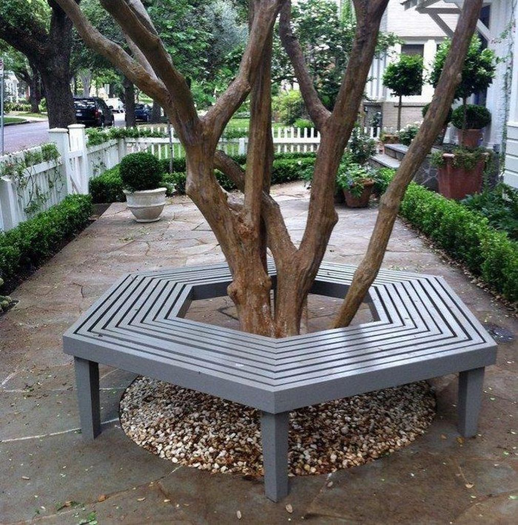 Light blue wooden benches that surround the tree