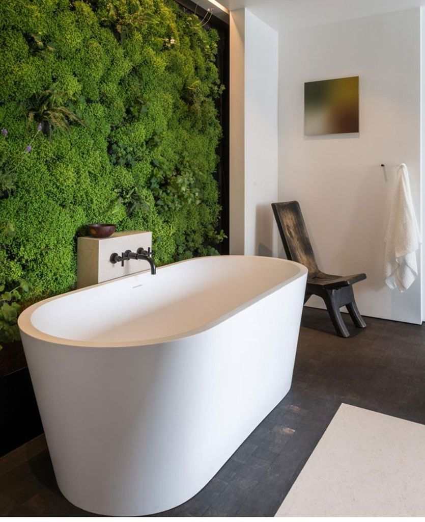 Modern bathroom design with white tub and white wall combined with moss on the wall to perfect your bathroom design