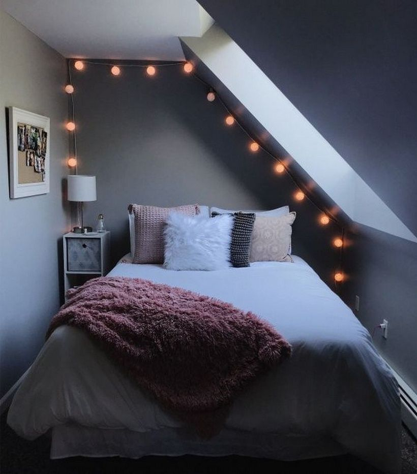 Modern girls room decor with white mattress, colorful pillows, pink blanket, storage and white lights in the corner and string lamp decorations