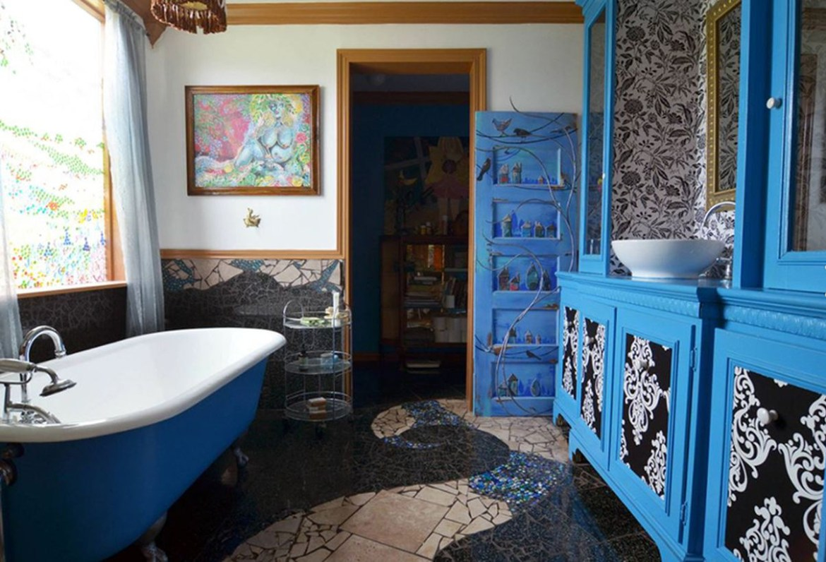 Unique boho bathroom decor with patterned tiles, blue wood storage and white and blue bathtub to look amazing