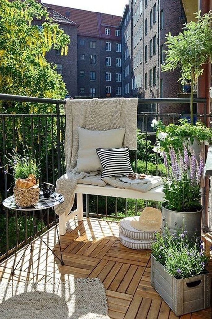Wooden floor and round table combined with plants decoratin for small balcony