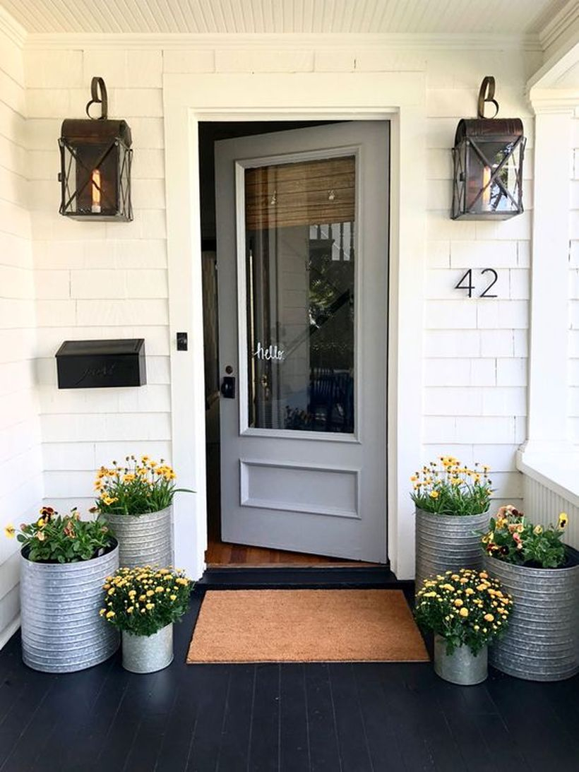Simple front door decoration with galvanized planters and blooming plants to create a cozy the porch