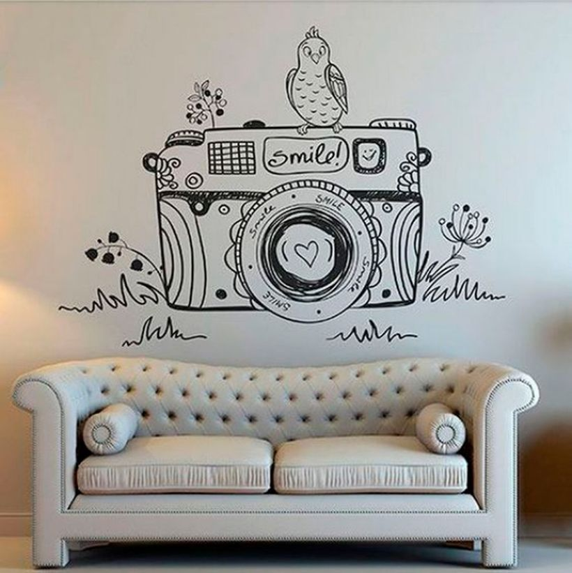 Small white living decor with wall painting unique camera theme on the wall