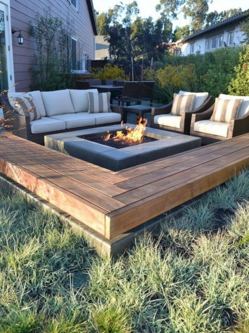 Square fire pit with white sofas and striped sofa cushions
