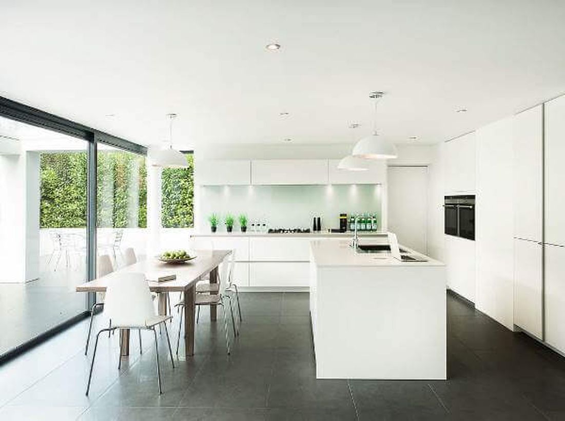 Black kitchen flooring with white island table, white cabinet, wooden table, and white chairs to look beautiful