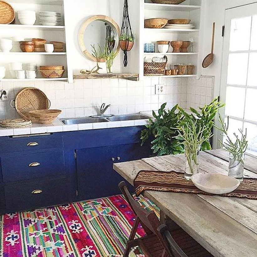 Colorful boho kitchen flooring with blue cabinet, white storage rack, wooden table and plants