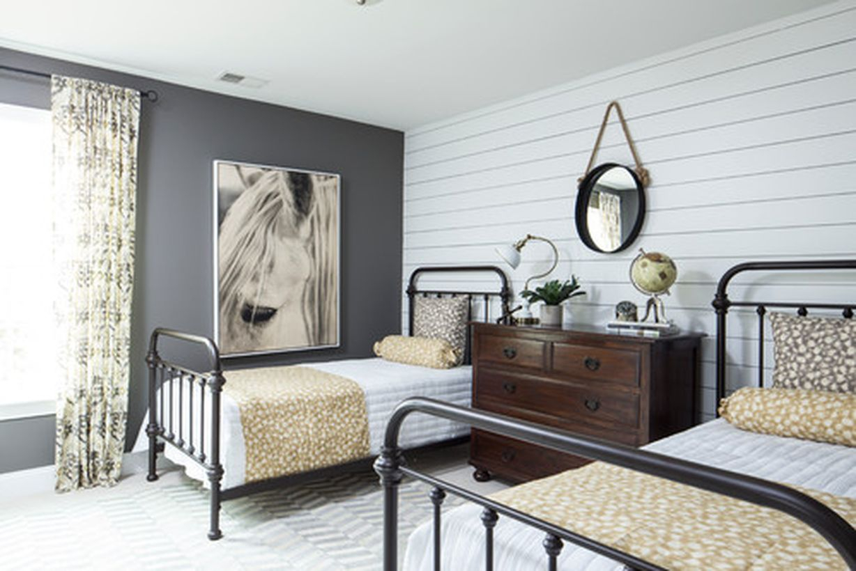 Easy bedroom with white bed, white wooden wall, and black iron bedstead to look impressive