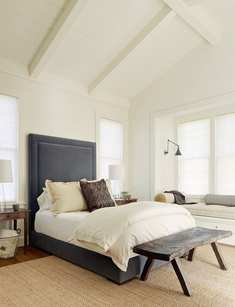 Impresiv bedroom with blue bedstead, white bed, white walls and square wooden chairs