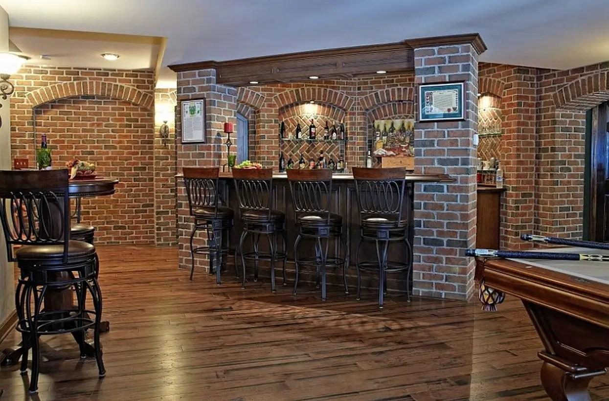 Pub style basement bar with a beautiful brick backdrop