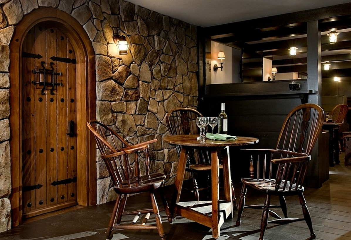 Basement makeove with stone wall, iron, and wooden chairs