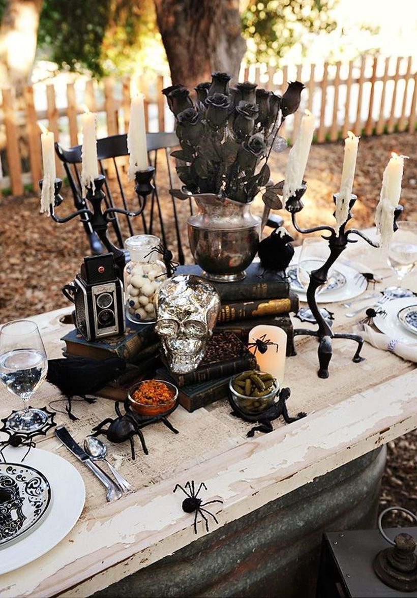 Black rose, iron black candle holder and black spider on dining table