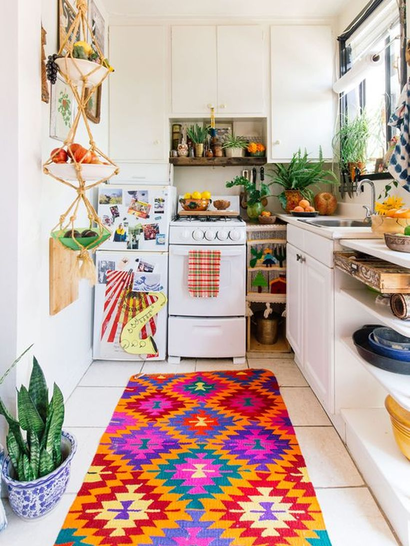 Boho pattern kitchen flooring with white cabinet, unique hanging storage and small pants on the pot