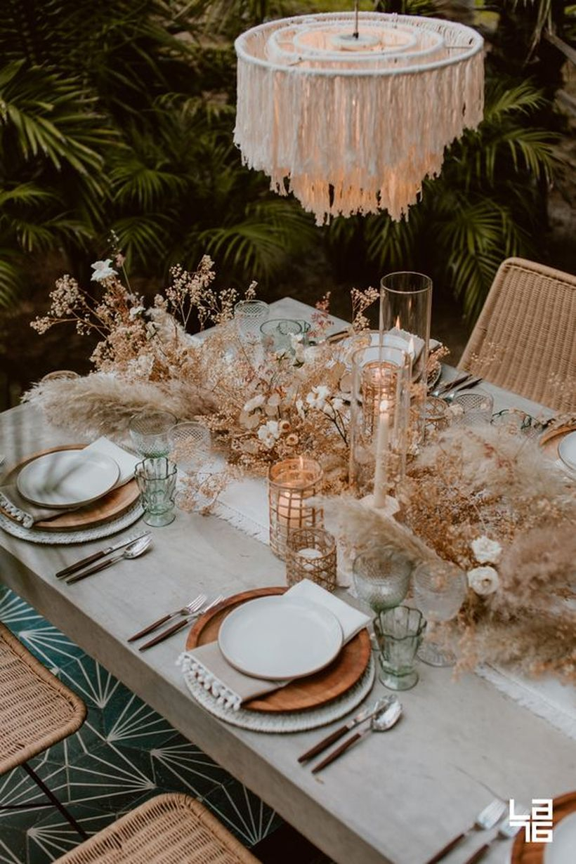 Boho tablescape with wooden plates, a fringe chandelier, candles, dried herbs and blooms plus pampas grass