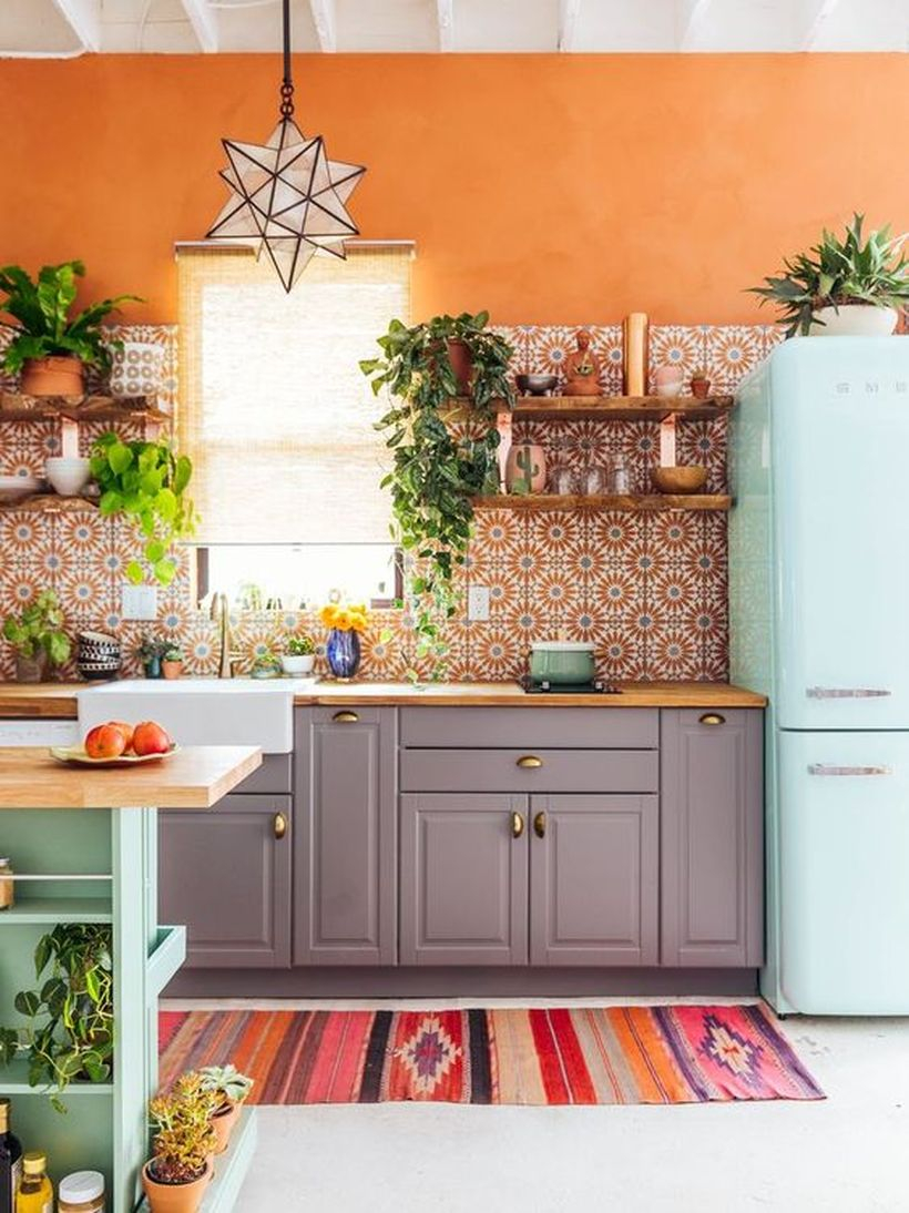 Colorful boho pattern flooring with gray wooden cabinet, wooden rack on the wall and small green plants