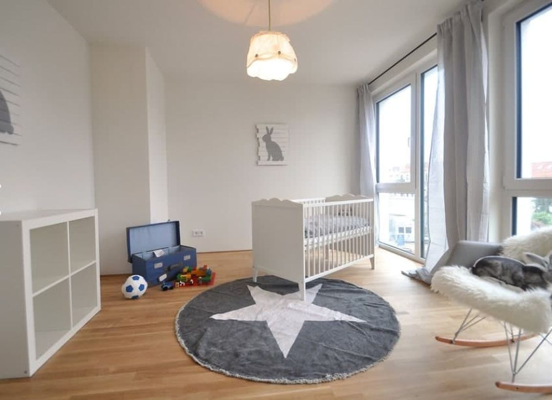 Large-monochrome-baby-boys-nursery-room-with-white-wooden-bed-big-rug-start-patterned-for-childrens-play-grounding