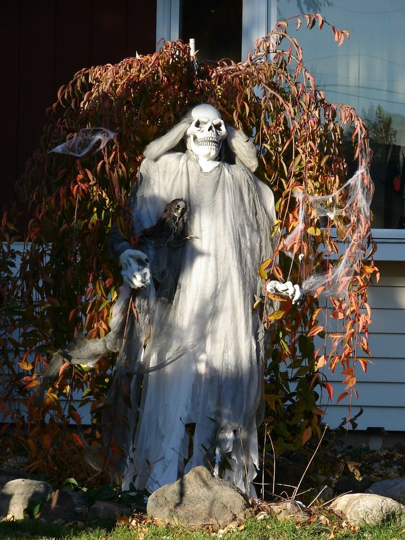 Outdoor halloween decoration creepy with a corpse character behind a tree