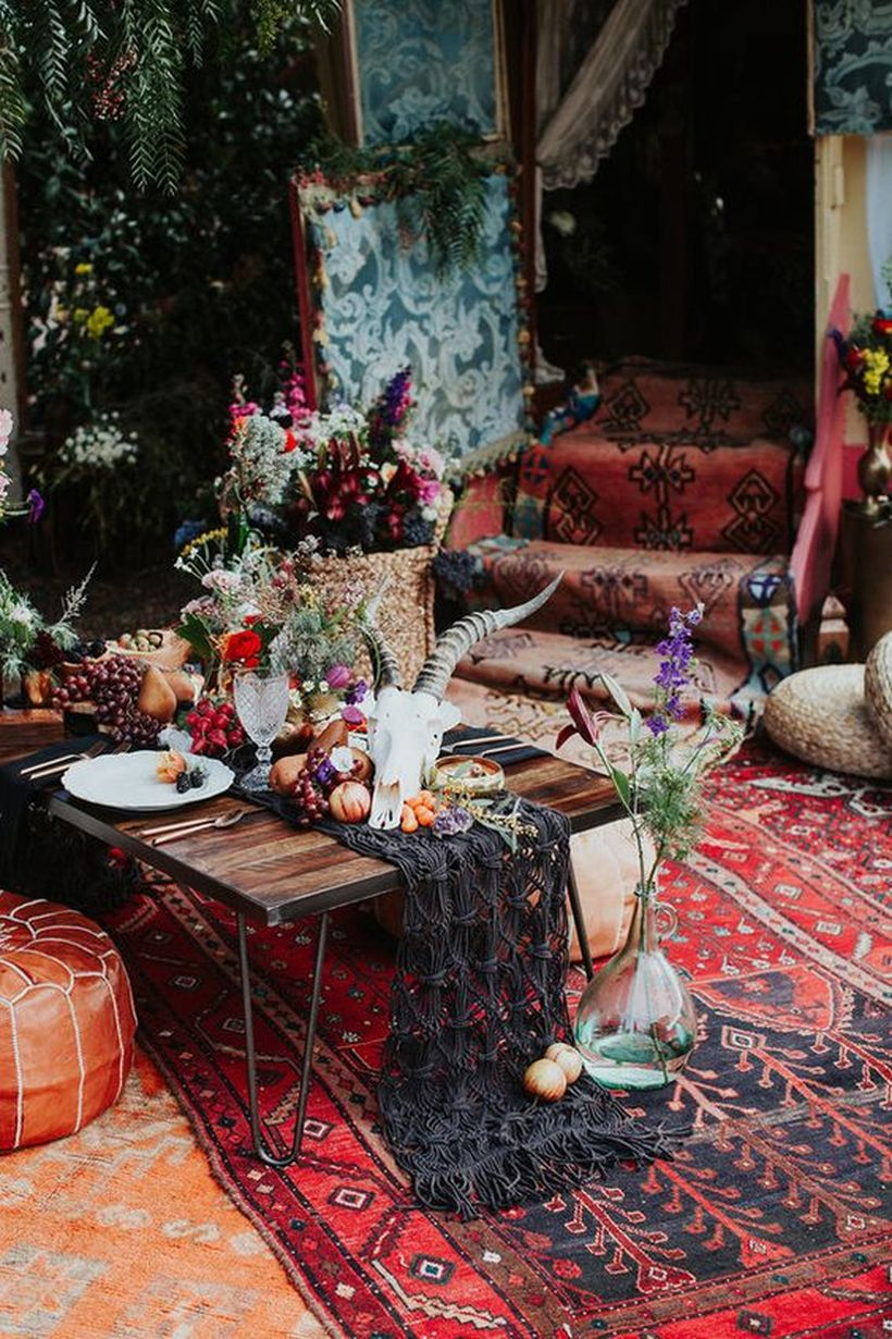 Picnic tablescape with a black macrame runner, an animal skull, fruits and veggies on top plus greenery