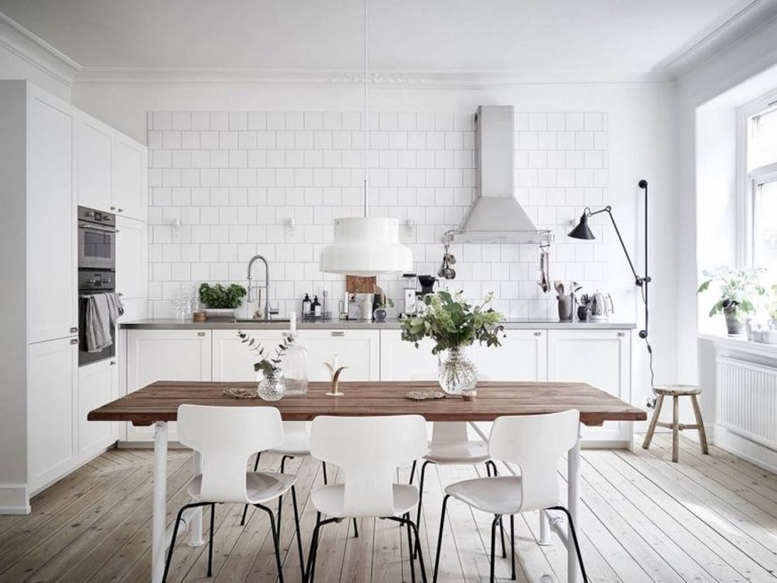 Scandinavian kitchen flooring with white cabinet, wooden table, white chairs and white walls
