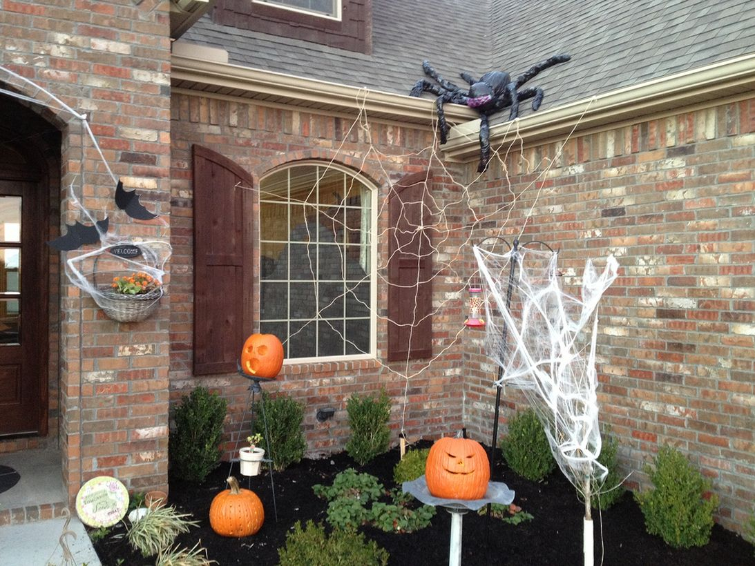 Simple outdoor halloween decoration with pumpkin and spider webs
