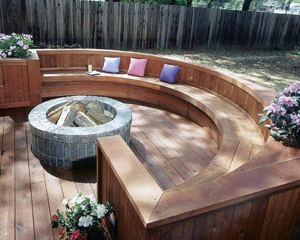 Backyard-patio-deck-design-with-brick-fire-pit-and-curved-wooden-bench-for-relaxing-with-family