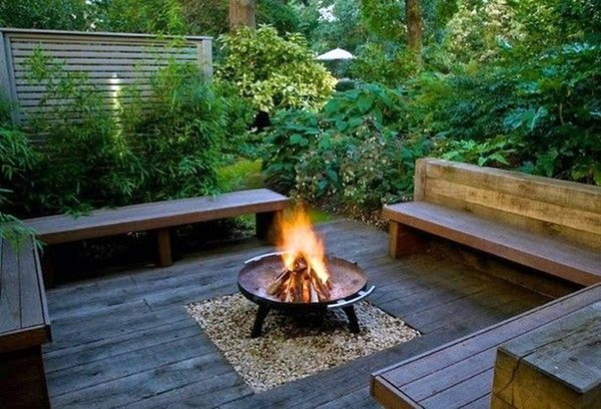 Diy-fire-pit-at-the-bottom-is-given-a-white-gravel-and-square-wooden-bech-in-your-backyard-patio-deck