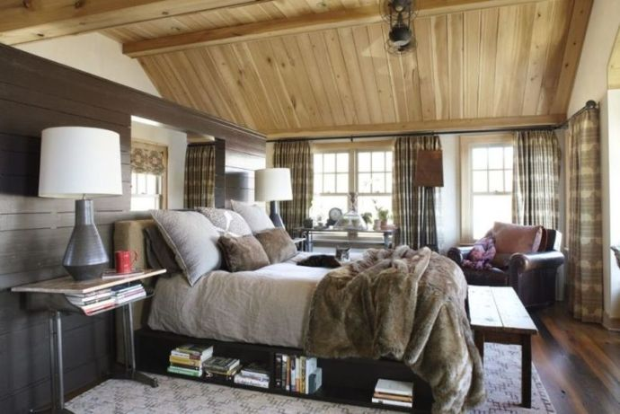 Farmhouse-bedroom-with-much-wood-printed-curtains-and-a-bed.-1