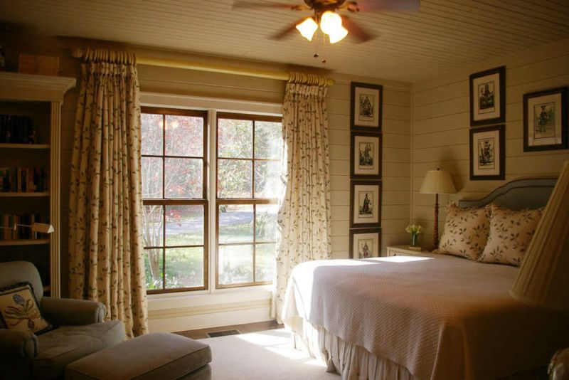 Farmhouse-bedroom-with-printed-textiles-and-many-artworks.-1