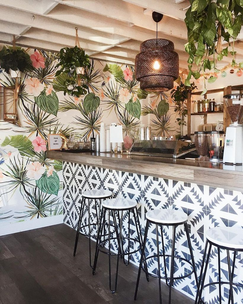 The decor of white patterned black coffee bars combined with unique chandeliers, green hanging plants, plant motifs within the white walls and small white korsi