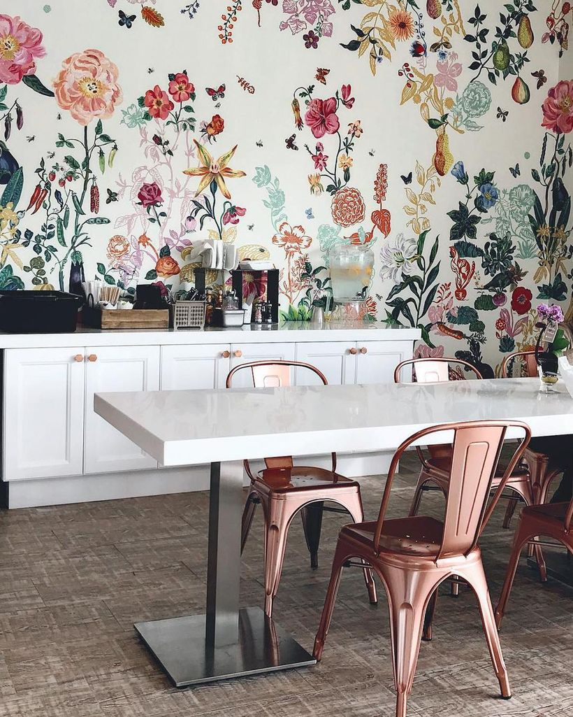 White coffee bar is combined with white plastic chairs and colorful floral designs inside the white walls