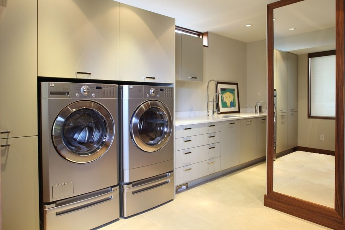 Laundry room with white cabinet and silver washing machine