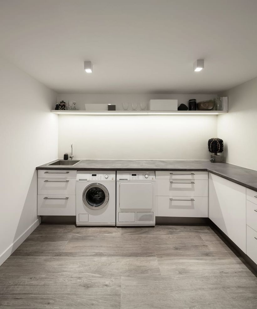 Laundry room with white cabinet and white rack