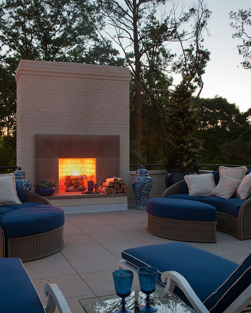 Modern-fire-pit-design-in-your-rooftop-with-the-position-of-the-blue-sofa-and-rattan-frame-to-warm-you-up-at-night