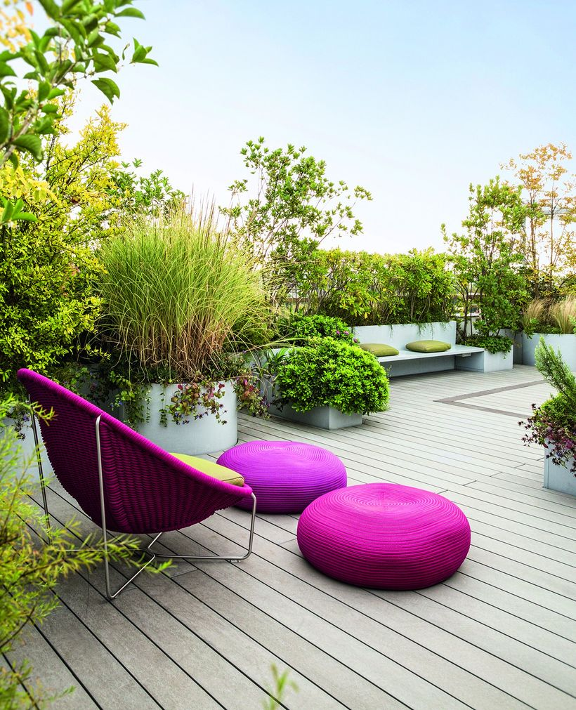 Smart-garden-arrangement-with-fresh-greenery-on-the-rooftop-and-red-lounge-chairs-to-relax