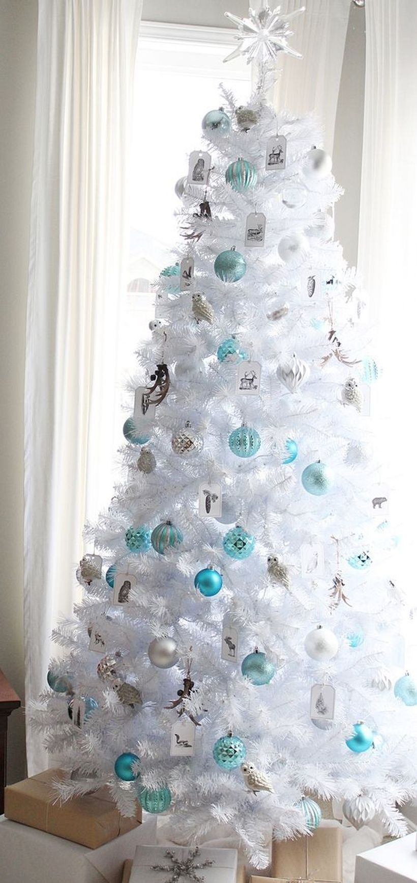 White-christmas-tree-decorated-in-blue-and-silver-bell-with-frost-and-star-ornament-at-the-top
