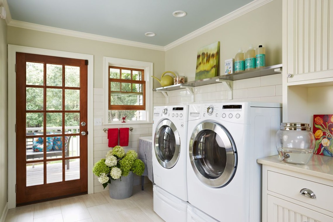 White laundry room with white cabinet and white washing machine