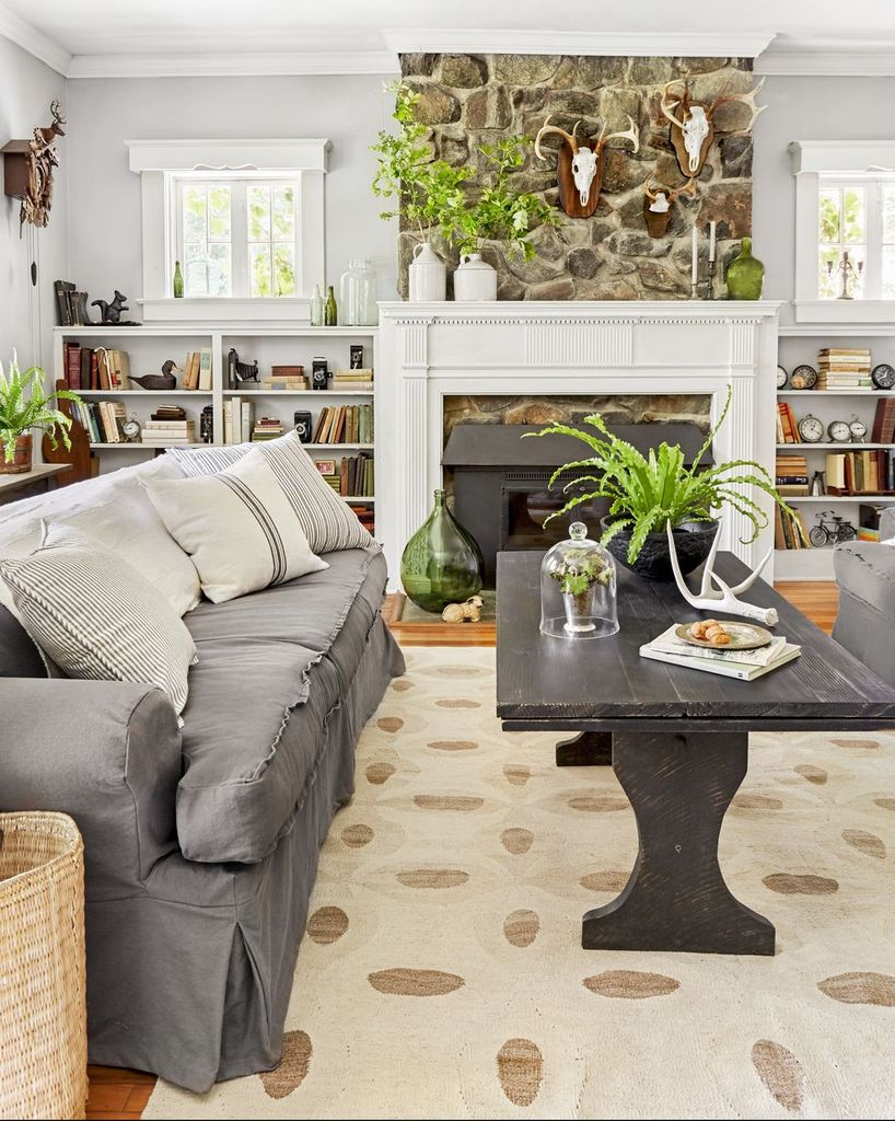 Farmhouse living room with dark grey sofa and black wooden table to perfect your living room design