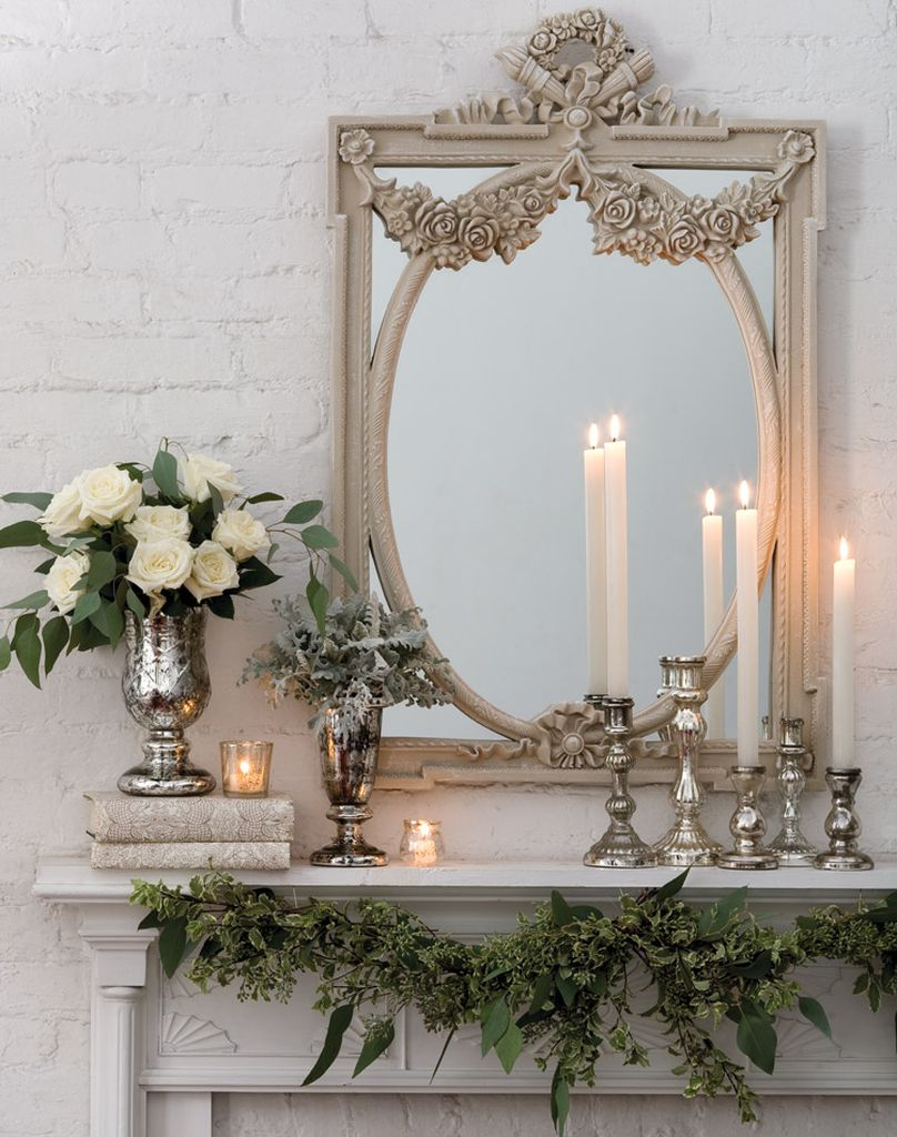Modern fireplace combined with white flowers and wintage mirror above it