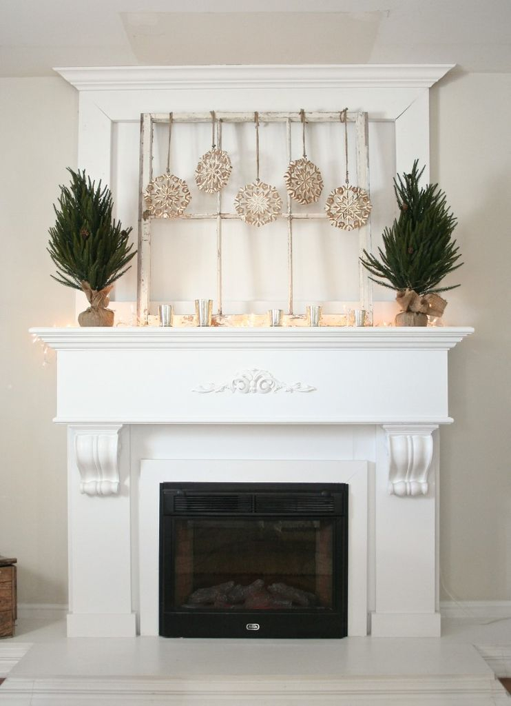 White fireplace with small tree and hanging gold decoration