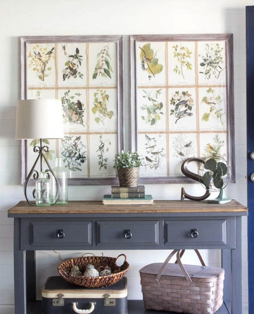 A grey console table with a stained tabletop, vintage posters as artworks, baskets and a potted plant for a cozy farmhouse entryway