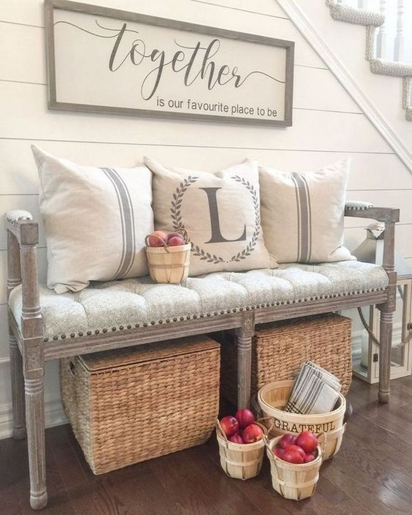 A vintage upholstered farmhouse bench, woven boxes, a sign and some wooden baskets
