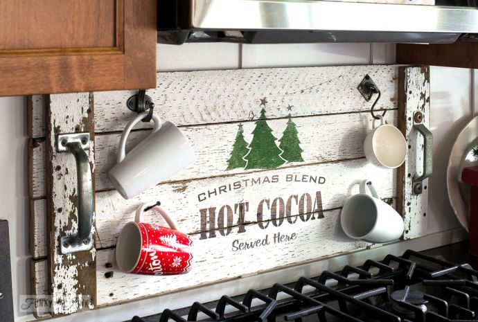Think-easy-like-hanging-up-a-hot-cocoa-christmas-tray-and-turning-it-into-a-festive-cup-holder-behind-the-stove.