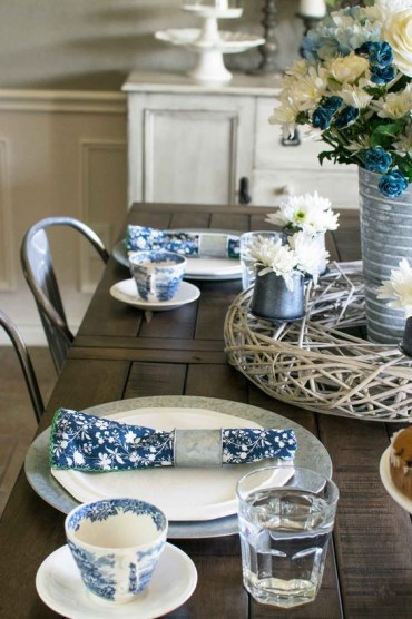 1 a-vintage-inspired-sprign-table-setting-with-navy-printed-napkins-a-white-and-blue-floral-centerpiece-and-printed-porcelain