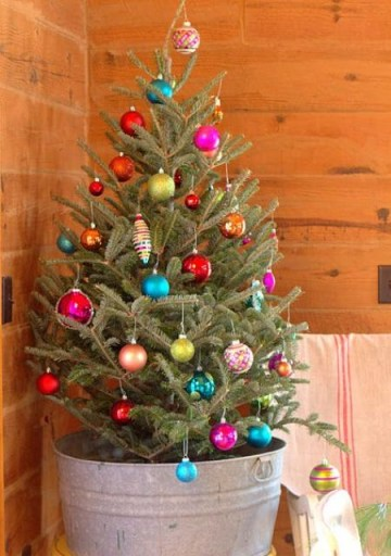 3 03-a-small-natural-tree-in-a-bucket-decorated-with-colorful-ornaments-looks-unusual