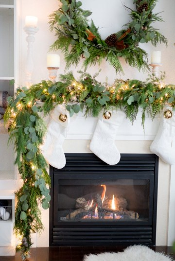 Real-garland-and-white-stockings-christmas-mantel_-686x1024