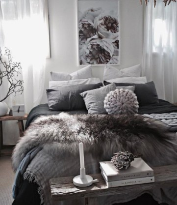 A-cozy-and-moody-bedroom-with-faux-fur-blankets-knit-blankets-and-a-rough-wood-bench-is-winter-reayd-and-very-trendy