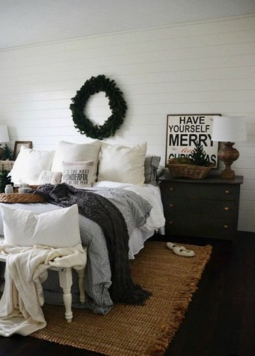 A-cozy-wintry-bedroom-with-knit-blankets-an-evergreen-wreath-a-christmas-tree-feels-veyr-cozy-and-chic