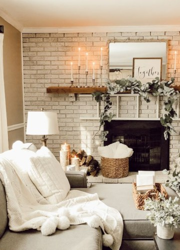 A-fireplace-deocrated-with-fresh-greenery-candles-and-some-firewood-by-its-side-for-a-cozy-feel