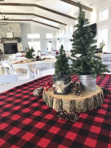 A-rustic-christmas-centerpiece-of-a-wood-slice-pinecones-and-mini-trees-in-buckets-plus-a-candle-lantern